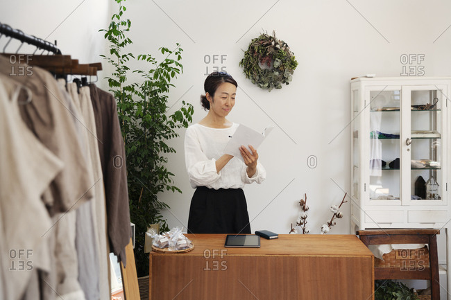 Japanese woman standing in a small fashion boutique, reading brochure.