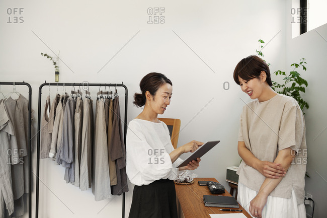 Two smiling Japanese women standing in a small fashion boutique, holding digital tablet.
