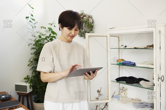 Japanese woman standing in a small fashion boutique, looking at digital tablet.