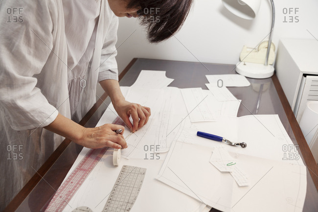Japanese woman wearing glasses working at a desk in a small fashion boutique.