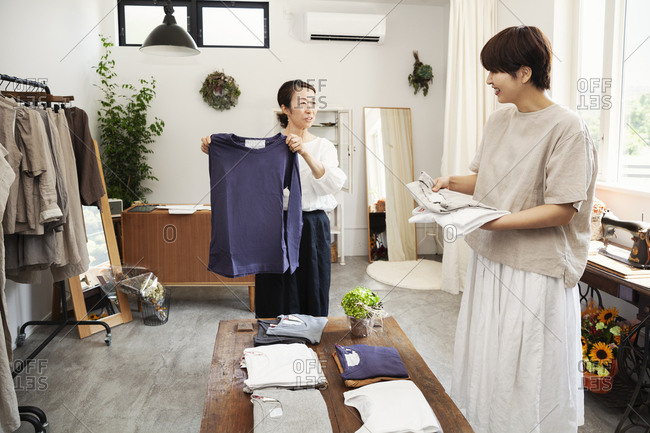 Two Japanese women standing in a small fashion boutique, arranging T-Shirts on a coffee table.