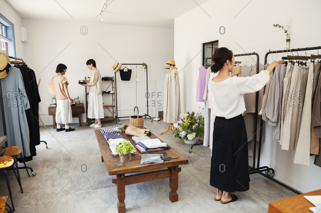 Three Japanese women standing in a small fashion boutique, looking at clothing on rails.