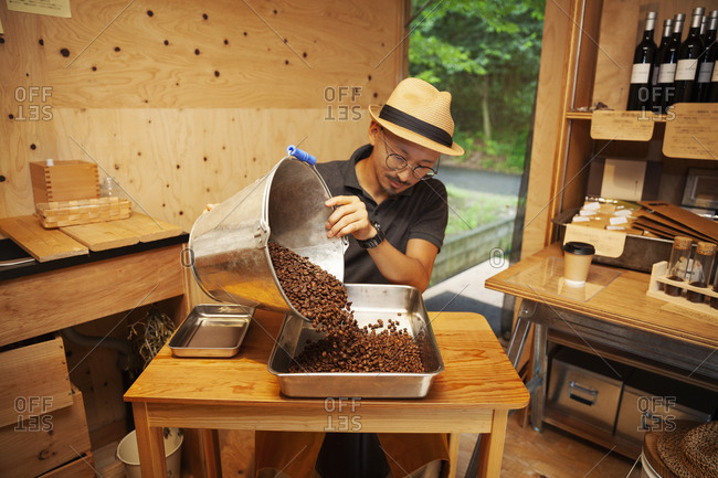 Japanese man wearing hat and glasses sitting in an Eco Cafe, pouring freshly roasted coffee beans into metal tray.