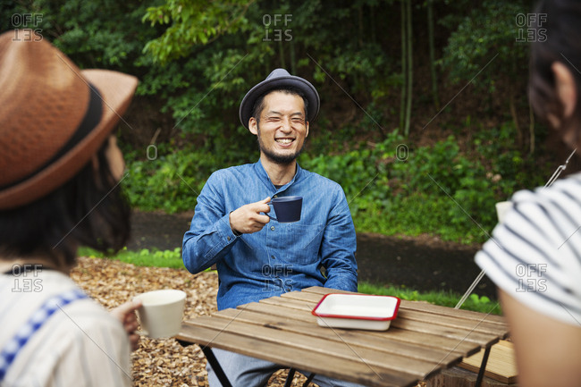 Japanese man and two women sitting outdoors at a table, drinking coffee.