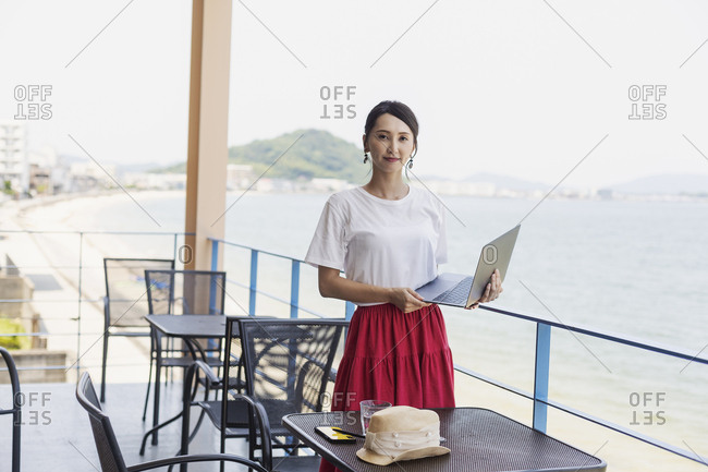 Female Japanese professional standing on balcony of a co-working space, holding laptop computer.