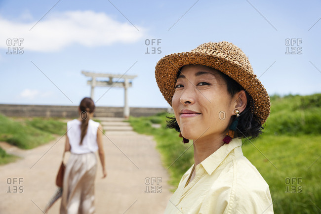 Two Japanese woman wearing hats standing on a path, Shinto shrine in the background.