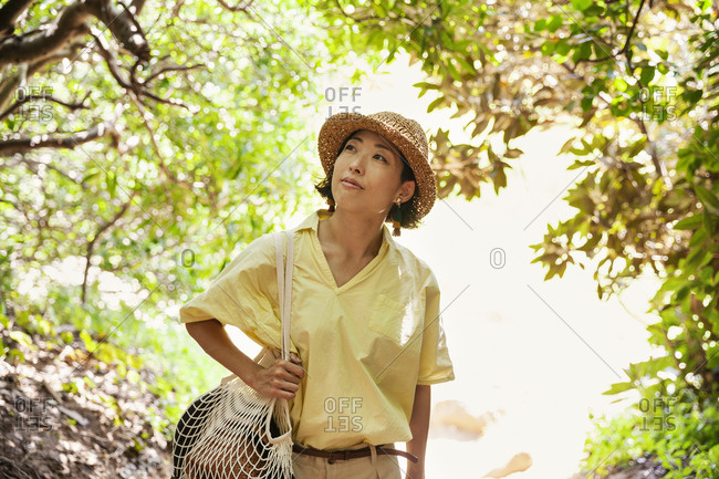 Japanese woman wearing hat hiking in a forest.