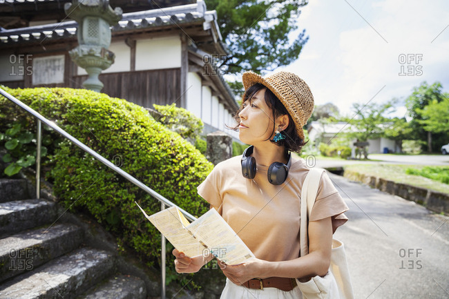 Japanese woman wearing hat and holding map standing outside Buddhist temple.