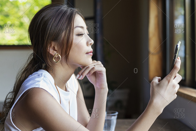 Japanese woman sitting at a table in a Japanese restaurant, using mobile phone.