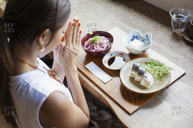 High angle view of Japanese woman sitting at a table in a Japanese restaurant, eating.