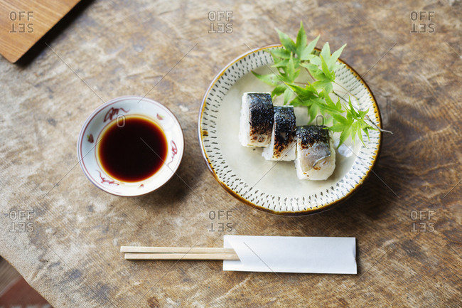 High angle close up of plate of Sushi and bowl of Soy Sauce on a table in Japanese restaurant.