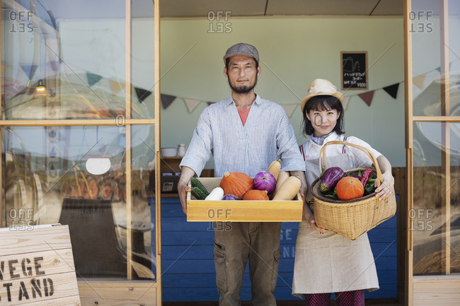 Japanese man and woman standing outside a farm shop, holding crate and basket with fresh vegetables, looking at camera.