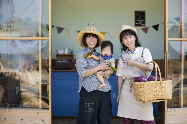 Two Japanese women and boy standing outside a farm shop, smiling at camera.