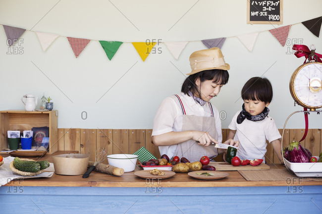 Japanese woman and boy standing in a farm shop, preparing food.