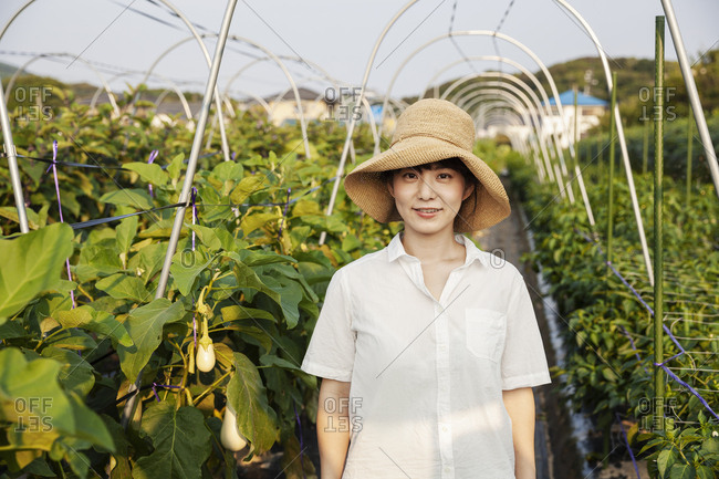 Japanese woman wearing hat standing in vegetable field, smiling at camera.