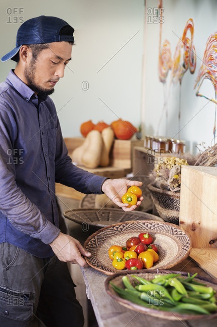 Japanese man wearing cap standing in farm shop, holding bowl with fresh vegetables.