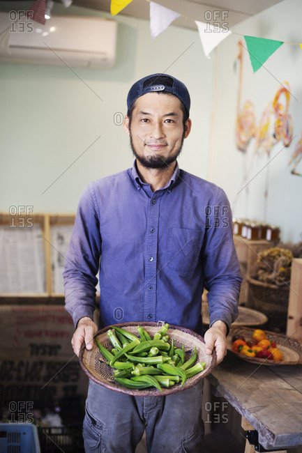 Smiling Japanese man wearing cap standing in farm shop, holding bowl with fresh okra.