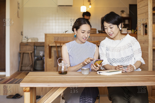 Two Japanese women sitting at a table in a vegetarian cafe, using mobile phone.