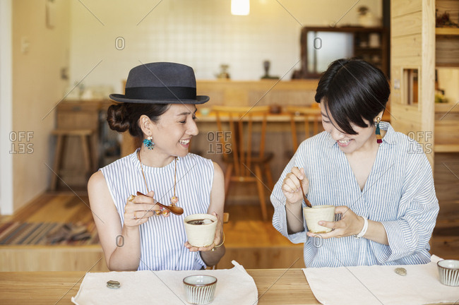 Two smiling Japanese women eating in a vegetarian cafe.