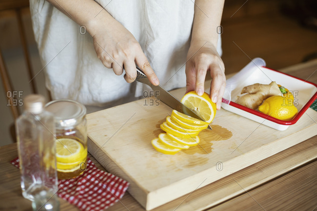 High angle close up of person cutting lemon with knife on wooden cutting board.