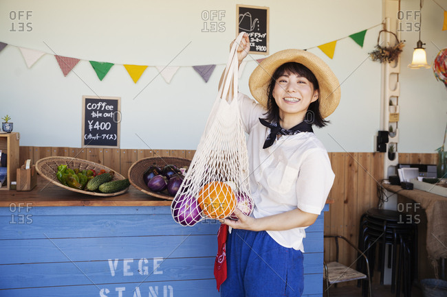 Japanese woman wearing hat working in a farm shop, smiling at camera.