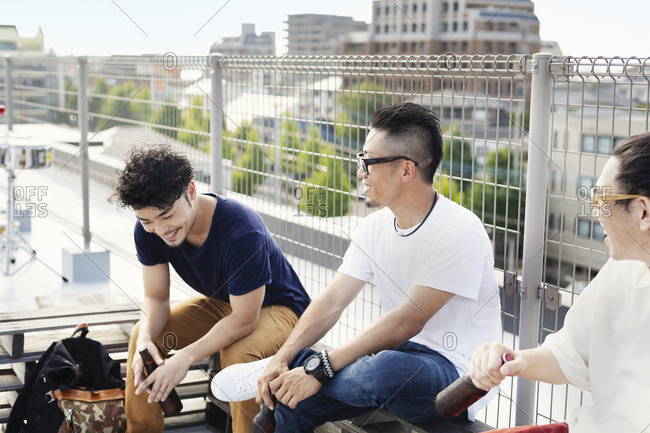 Three young Japanese men sitting on a rooftop in an urban setting, drinking beer.