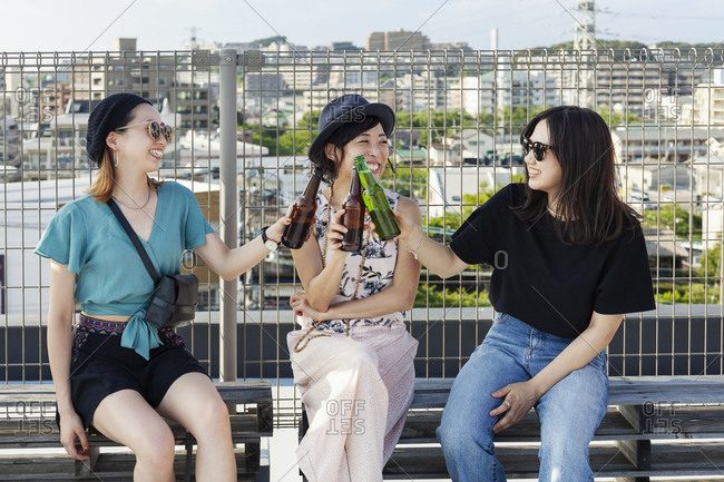 Three young Japanese women sitting on a rooftop in an urban setting, drinking beer.