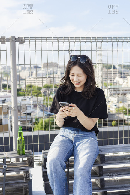 Young Japanese woman sitting on a rooftop in an urban setting, using mobile phone.