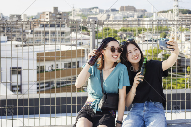 Two young Japanese women sitting on a rooftop in an urban setting, taking selfie with mobile phone.