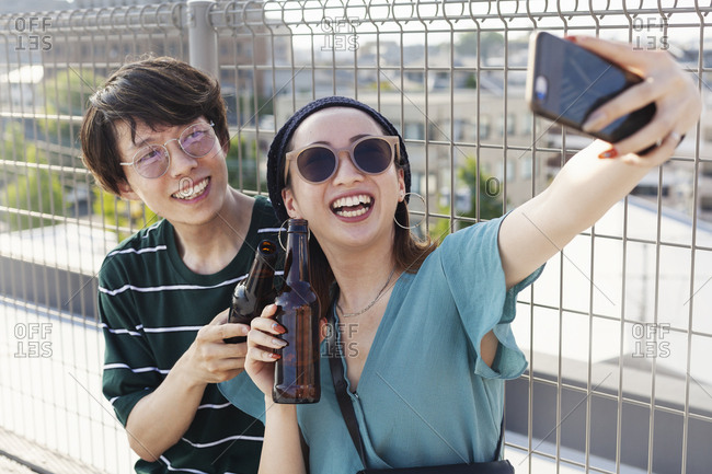 Young Japanese man and woman sitting on a rooftop in an urban setting, taking selfie with mobile phone.