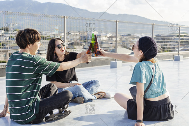 Young Japanese man and two women sitting on a rooftop in an urban setting, drinking beer.