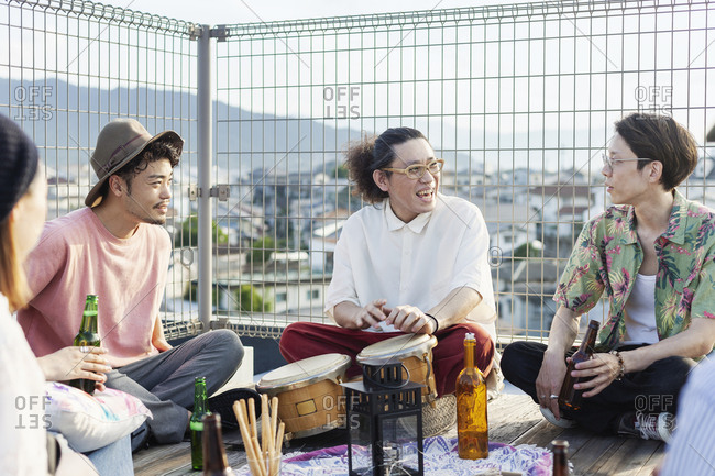 Group of young Japanese men and women sitting on a rooftop in an urban setting, drinking beer.