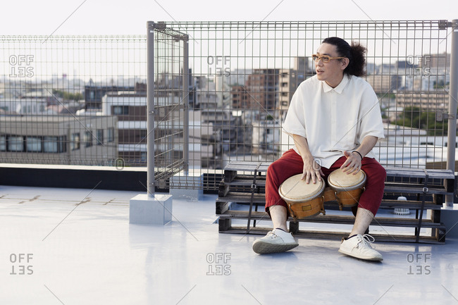 Japanese man sitting on a rooftop in an urban setting, playing drums.