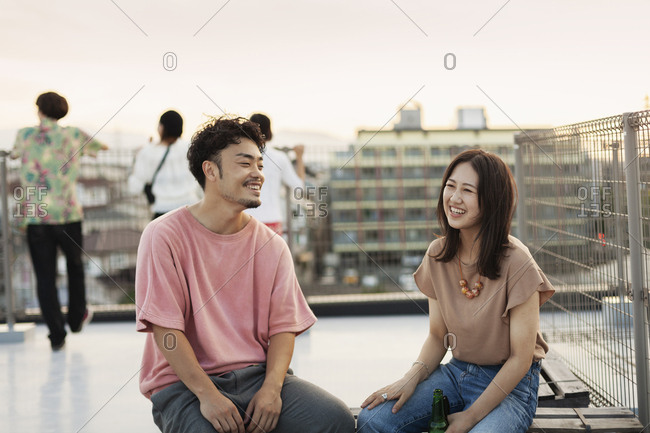 Smiling young Japanese man and woman sitting on a rooftop in an urban setting.