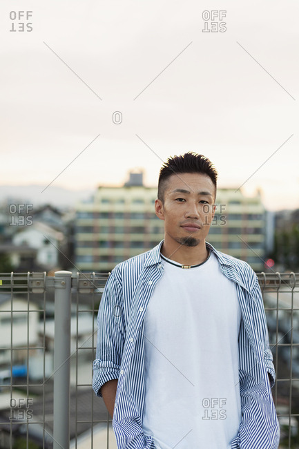Young Japanese man standing on a rooftop in an urban setting, looking at camera.