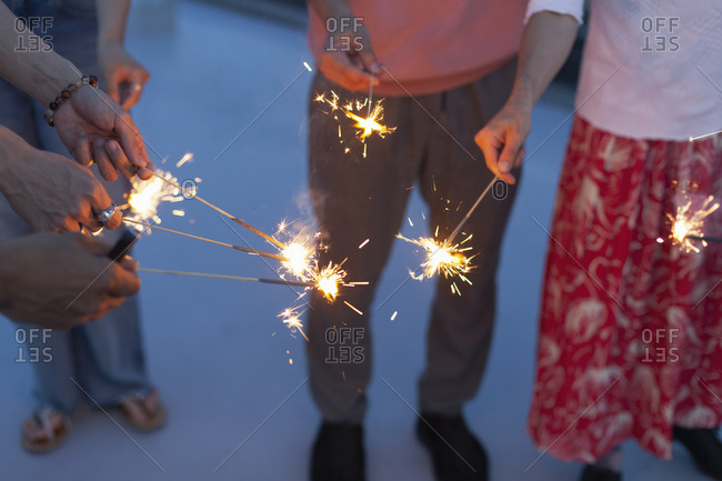 Group of young men and women with sparklers on a rooftop in an urban setting.