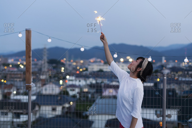 Smiling young Japanese woman holding sparkler on a rooftop in an urban setting.