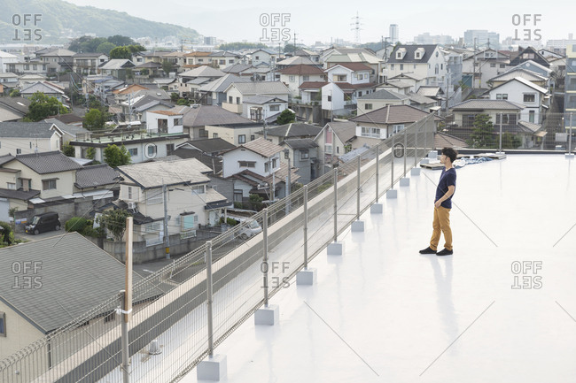 High angle view of Japanese man standing on a rooftop in an urban setting.