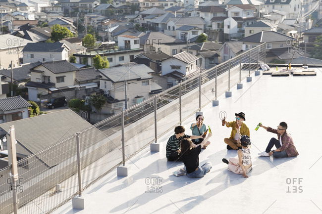 High angle view of group of young Japanese men and women sitting on a rooftop in an urban setting.