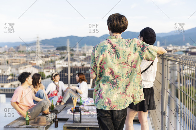 Group of young Japanese men and women on a rooftop in an urban setting.