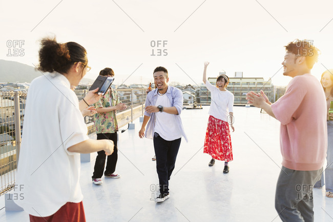 Group of young Japanese men and women dancing on a rooftop in an urban setting.