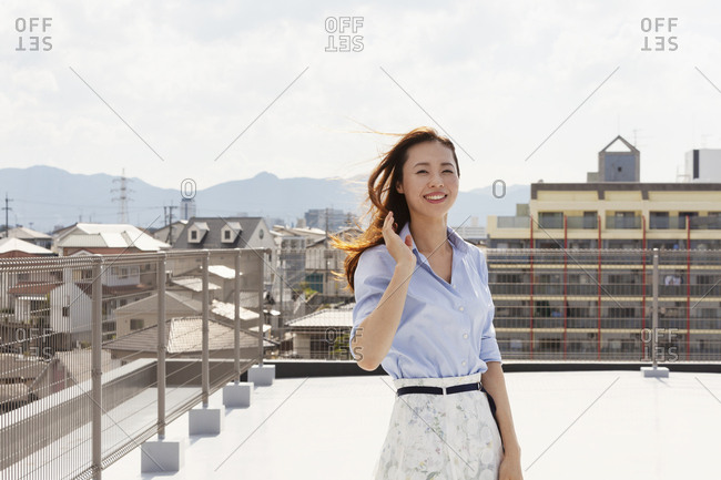 Young Japanese woman standing on a rooftop in an urban setting, looking at camera.