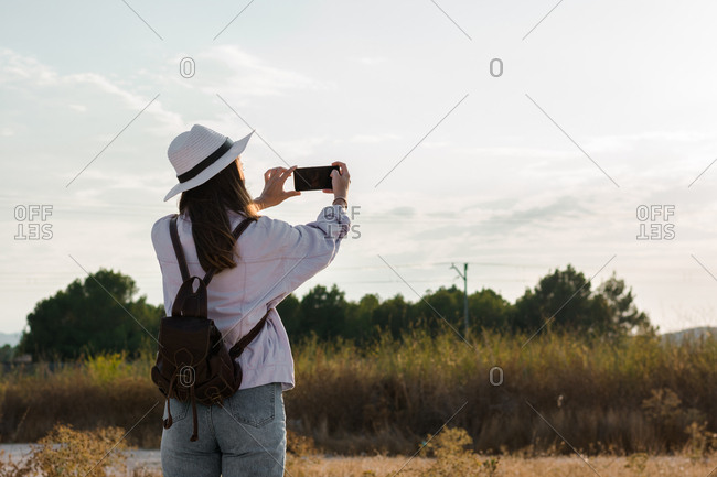 Young woman is taking a picture with her smartphone in a field. Adventure, technology