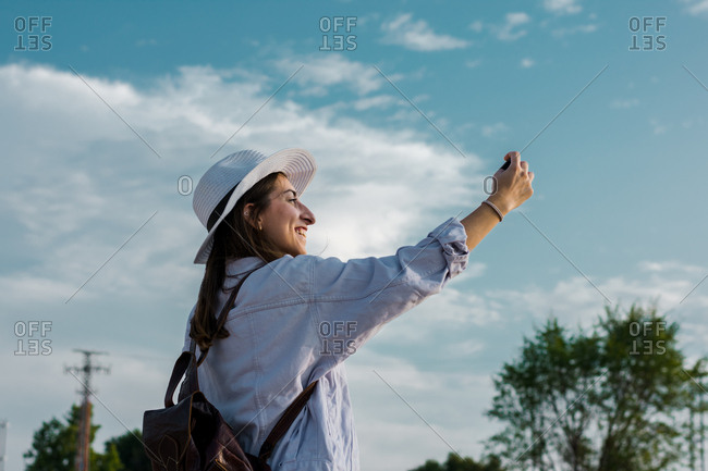 Young woman is taking a self portrait with her smartphone. Travel, lifestyle