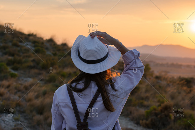 Young woman is walking on the mountain with a hat and her backpack. Travel, adventure, lifestyle