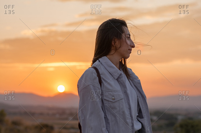 Young adventurer woman on a mountain at sunset. Lifestyle concept, portrait