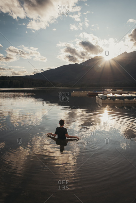 Teenage boy standing in a lake looking at sun setting on a mountain.