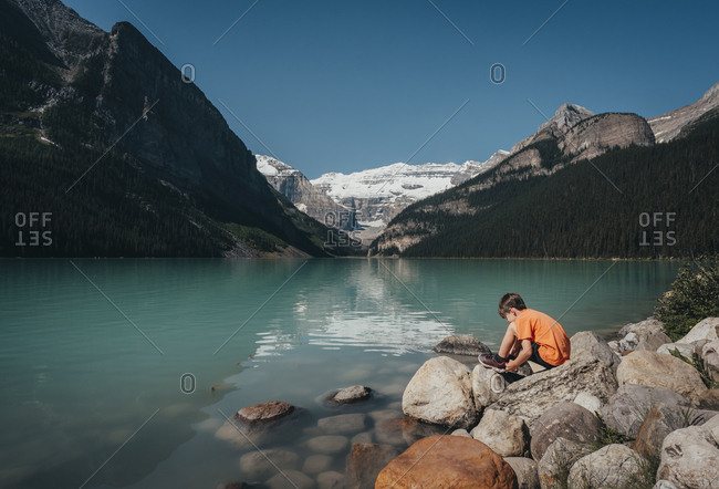 Young boy sitting on rocky shoreline of Lake Louise in the mountains.