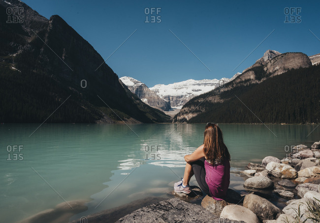 Woman sitting on shoreline of Lake Louise in the Rocky Mountains.