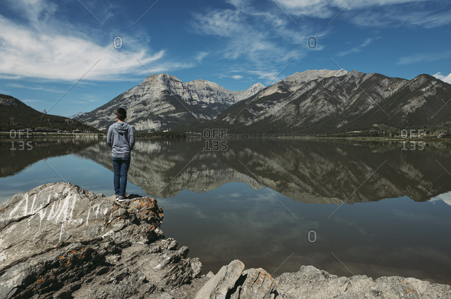 Boy standing on rocky ledge overlooking a lake and mountain vista.